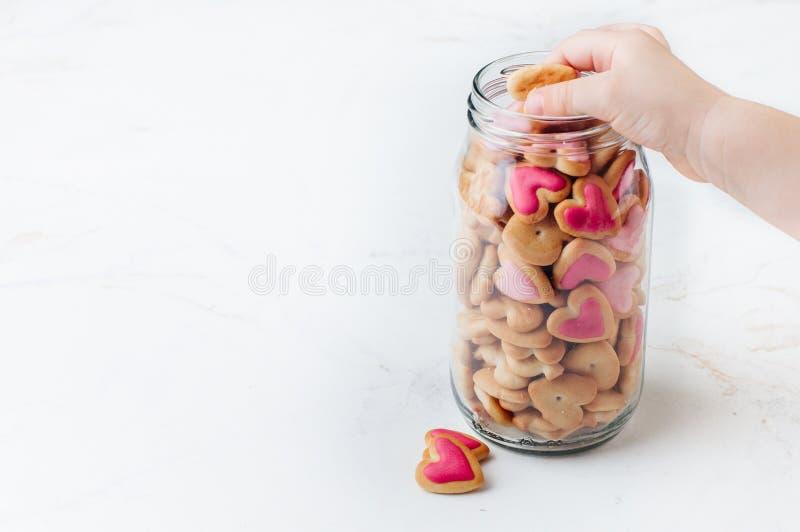 I bambini passano la presa dei biscotti di forma del cuore dal barattolo di vetro su fondo leggero fotografie stock