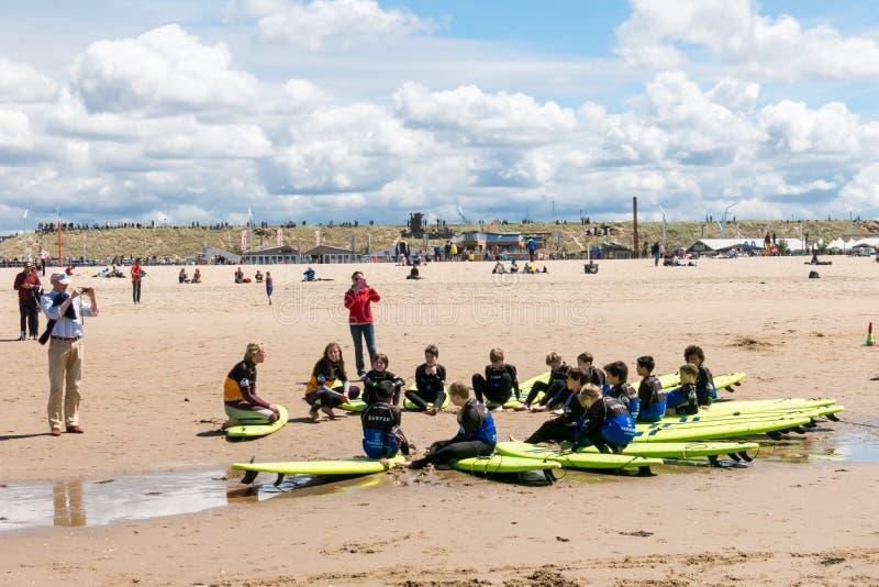 I bambini praticano il surfing le lezioni sulla spiaggia di Scheveningen, L'aia, Paesi Bassi fotografia stock
