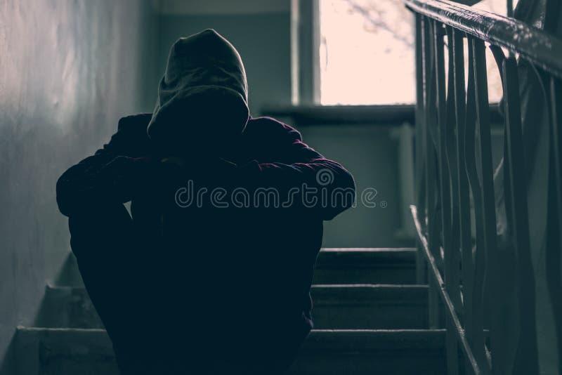 I bambini problema, ragazzino si siedono sulle scale su costruzione abbandonata f fotografia stock