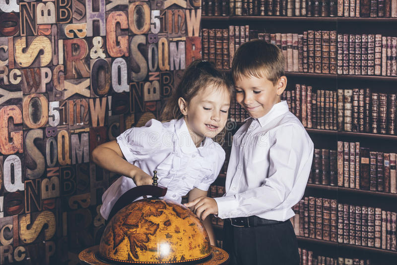 I bambini ragazzo e ragazza dell'età scolare considerano un globo fotografia stock
