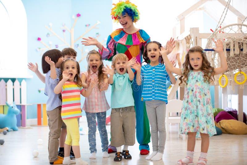 I bambini raggruppano con il pagliaccio che celebra la festa di compleanno fotografia stock