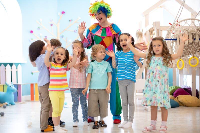 I bambini raggruppano con il pagliaccio che celebra la festa di compleanno fotografia stock libera da diritti