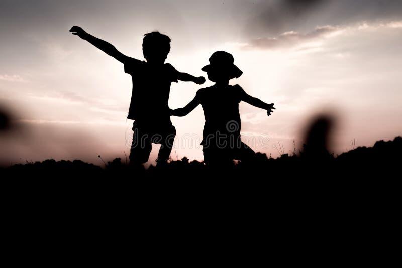 I bambini saltano giù una collina che solleva le mani sul livello fotografia stock
