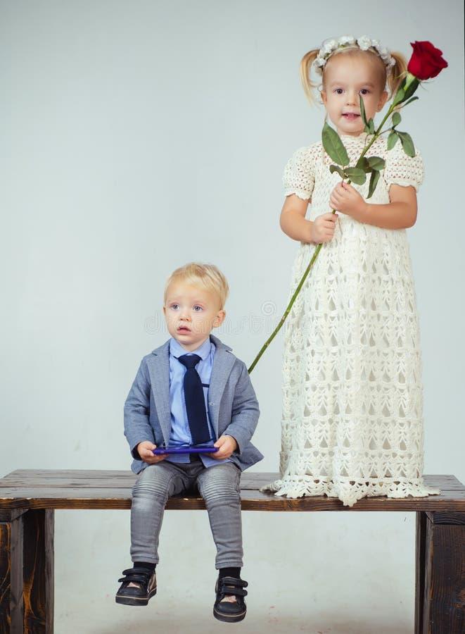 I bambini si accoppiano nell'amore retro data delle coppie Rosa rossa Infanzia felice Legami di famiglia piccolo bambino con la r immagine stock
