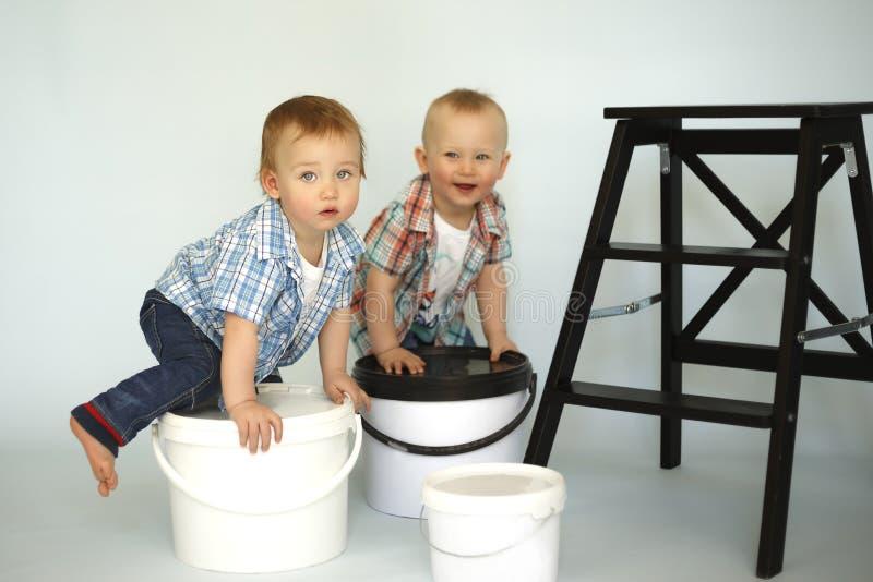 I bambini si siedono sulle grandi latte di pittura immagini stock