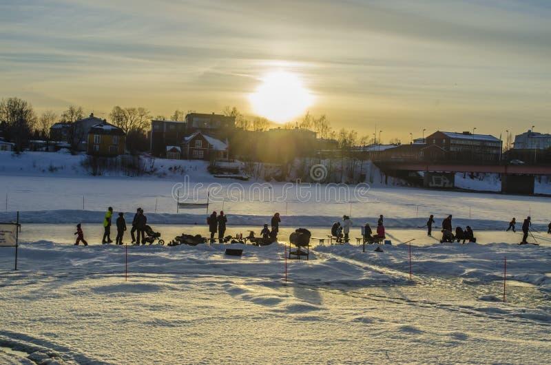 I bambini stanno godendo del gioco sul fiume congelato con la loro famiglia fotografie stock libere da diritti