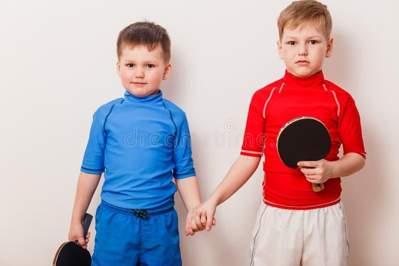I bambini stanno tenendo la racchetta per ping-pong su fondo bianco immagine stock