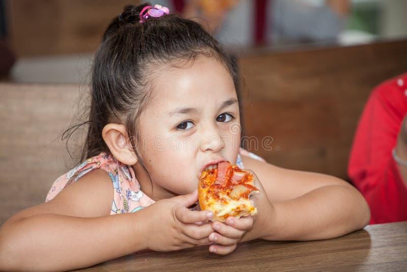 I bambini svegli della bambina godono di di mangiare la pizza a scuola dell'aula bambino affamato immagine stock
