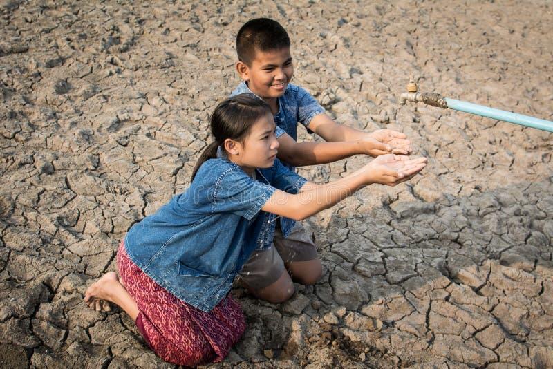 I bambini tristi vogliono bere una certa acqua sulla terra della crepa fotografia stock