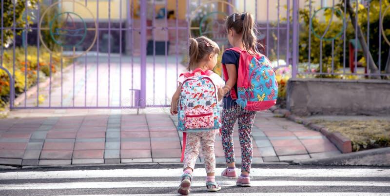 I bambini vanno a scuola, studenti felici con gli zainhi e tenersi per mano della scuola insieme immagine stock
