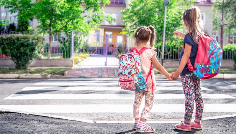 I bambini vanno a scuola, studenti felici con gli zainhi e tenersi per mano della scuola insieme fotografia stock