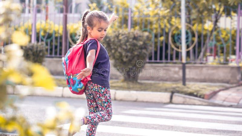 I bambini vanno a scuola, uno studente felice con uno zaino, incroci fotografia stock libera da diritti