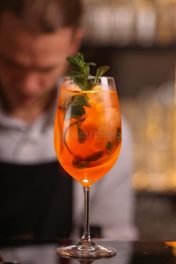 I baristi sta facendo Aperol Spritz il cocktail Aperol Spritz il cocktail dell'alcool sulla superficie nera del fondo fotografia stock