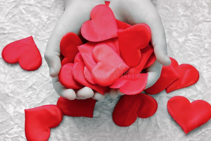 I barns händer mycket dekorativa hjärtor Bukett av rosor i bakgrunden arkivbild