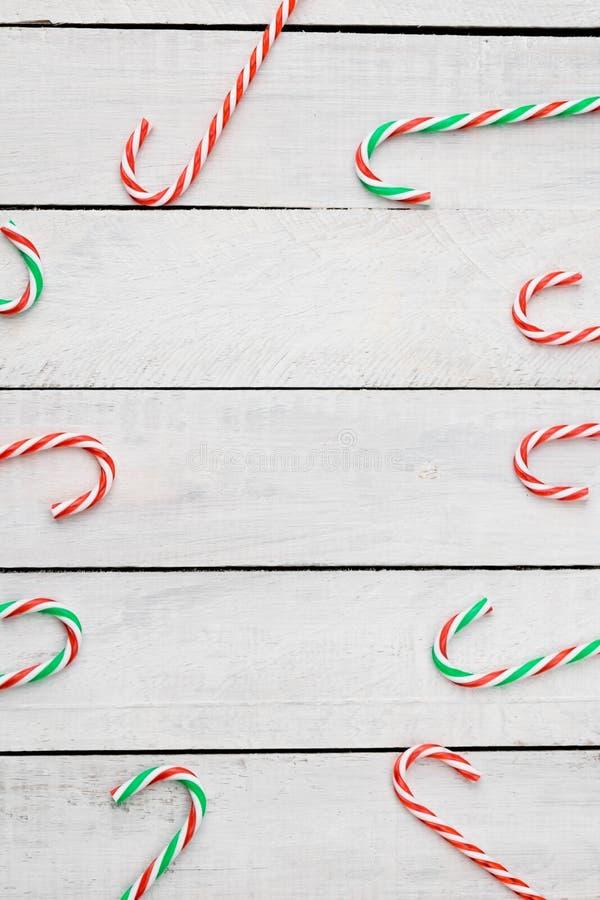 I bastoncini di zucchero mettono su pianamente il fondo di legno bianco Decorazione anno di nuovo e di natale Spazio per testo immagine stock libera da diritti