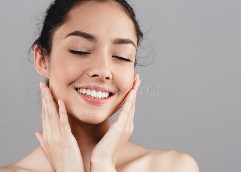 I bei denti del fronte di bellezza dello skincare della donna sorridono con il handsclo immagini stock