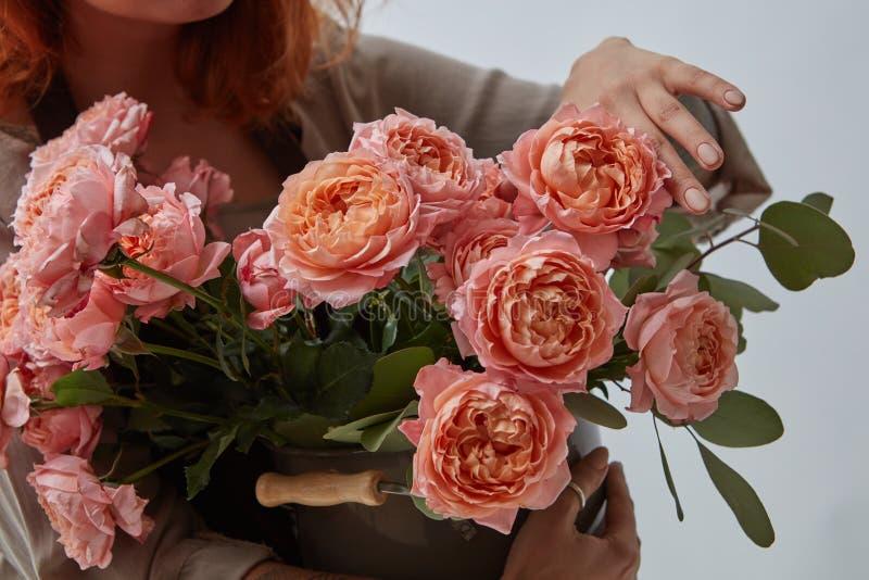 I bei fiori rosa stanno tenendo le mani femminili su un fondo grigio Giorno felice del `s del biglietto di S immagine stock libera da diritti