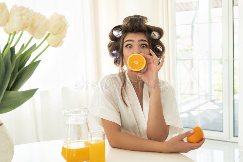 I bei giovani hanno sorpreso la donna castana in bigodini che tengono un'arancia vicino alla sua bocca ed un altro in sua mano de fotografie stock