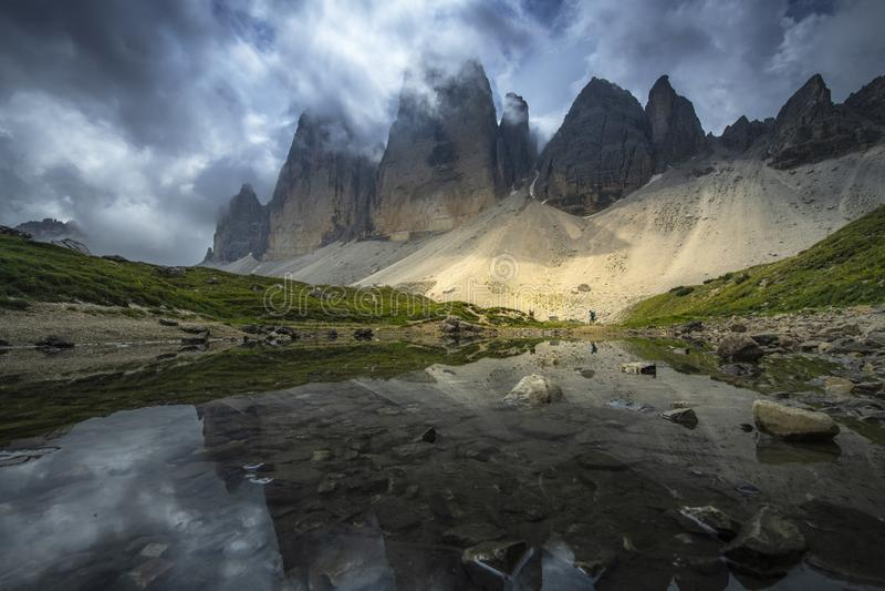 I bei paesaggi osservano della riflessione della montagna sul fiume con cielo blu sull'estate da Tre Cime, le dolomia, Italia fotografie stock