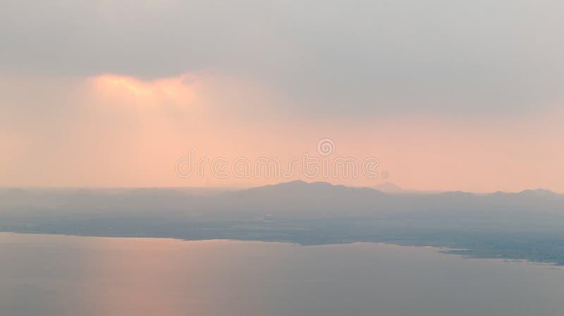 I bei raggi di Sun con si rannuvola le montagne e la diga immagini stock libere da diritti