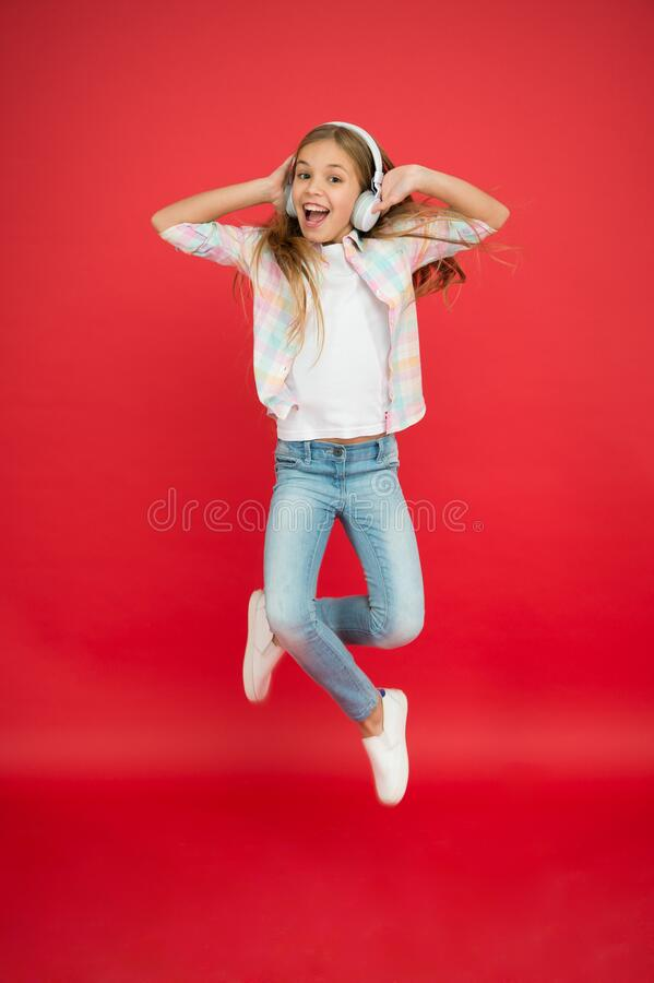 I believe i can fly. Girl listening music modern gadget. Kid happy with wireless headset dancing jumping. Stereo. Headphones. Kid using modern technology royalty free stock image