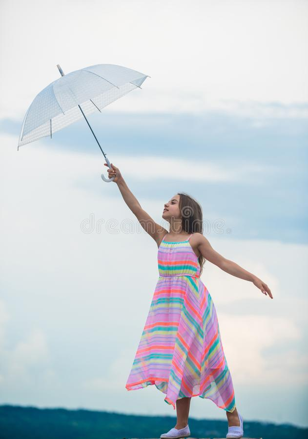 I believe i can fly. Touch sky. Girl with light umbrella. Fairy tale character. Happy childhood. Feeling light. Anti. Gravitation. Fly drop parachute. Dreaming stock image