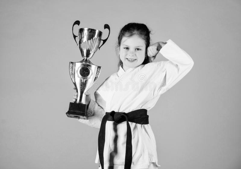 I am the best. knockout. energy and activity for kids. practicing Kung Fu. happy childhood. sport success in single. Combat. girl with champion cup. martial royalty free stock photo
