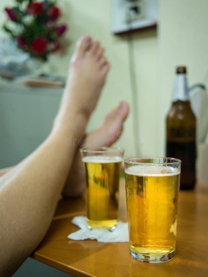 I bevitori di birra ritengono soddisfatti e rilassati di un assaggio della birra dopo la degustazione delle varie marche fotografia stock