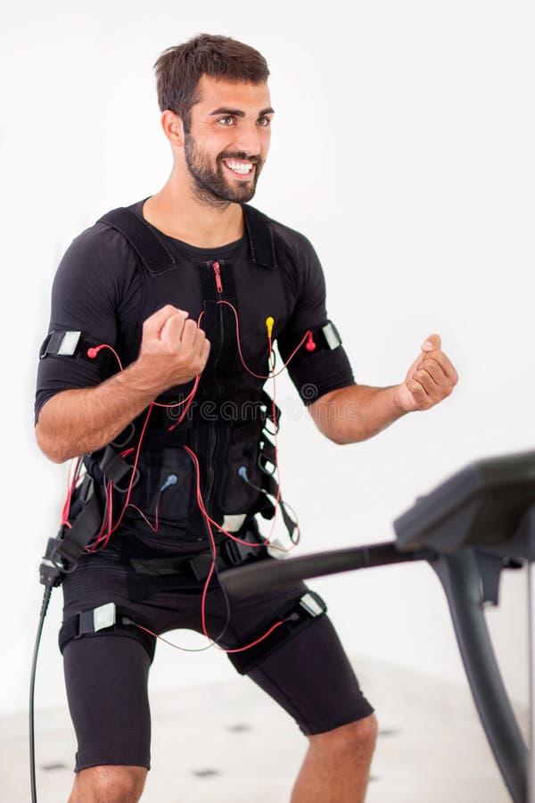 I bicipiti adatti di esercizio dell'uomo dei giovani arricciano su elettro stimulat muscolare fotografie stock libere da diritti