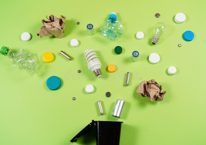I bidoni della spazzatura e l'immondizia assortita isolati su verde, riciclano il conce fotografia stock