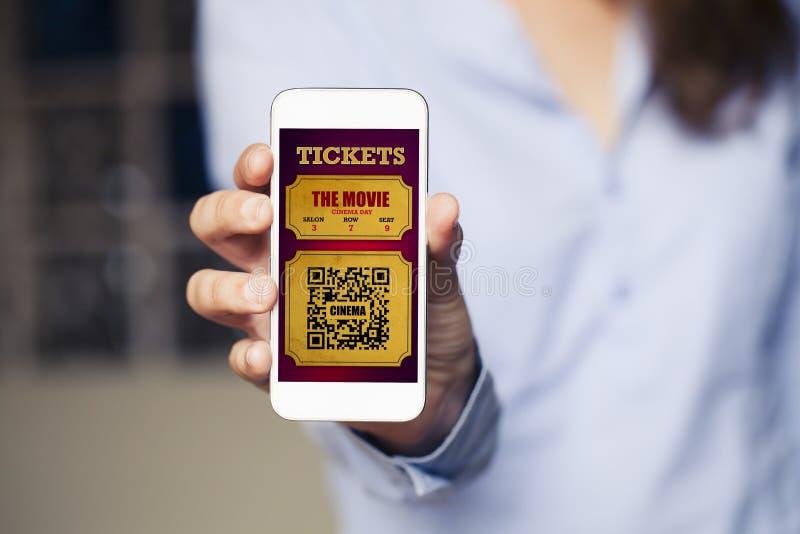 I biglietti del cinema in un telefono cellulare schermano mentre la donna lo tiene fotografia stock