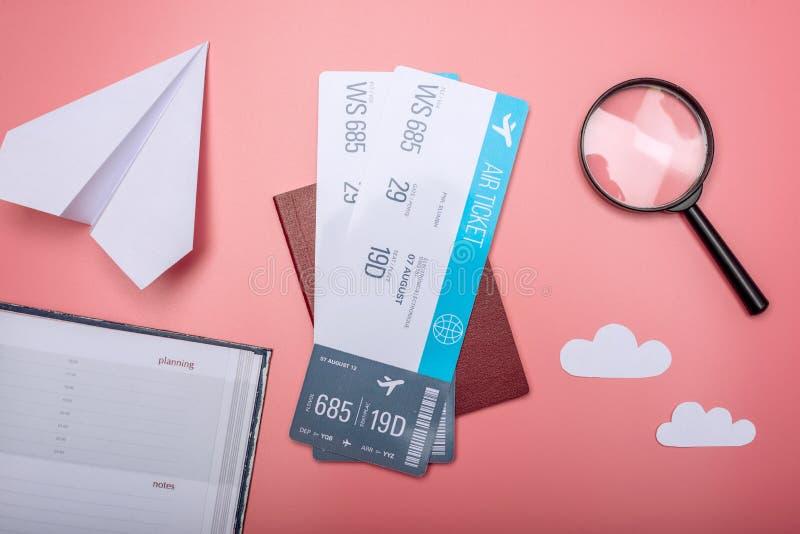 I biglietti di aria con il passaporto e la carta spianano su fondo rosa, a immagine stock