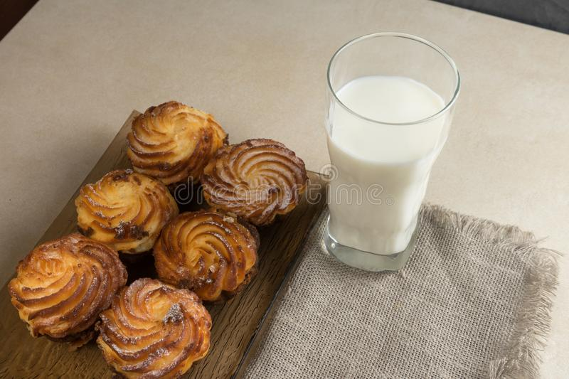 I bigné della torta di formaggio del cioccolato e un bicchiere di latte per la prima colazione copiano lo spase fotografie stock libere da diritti