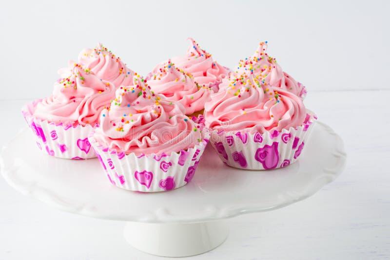I bigné rosa decorati di compleanno sul dolce stanno fotografia stock