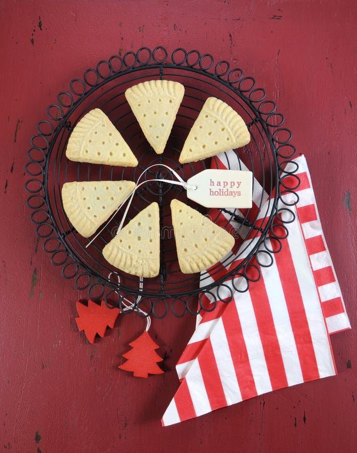 I biscotti del triangolo di biscotto al burro di Natale su cottura d'annata tormentano su legno rustico rosso scuro - verticale immagini stock libere da diritti