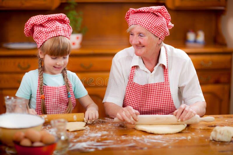 I biscotti di cottura della nipote e della nonna preparano la pasta fotografia stock libera da diritti