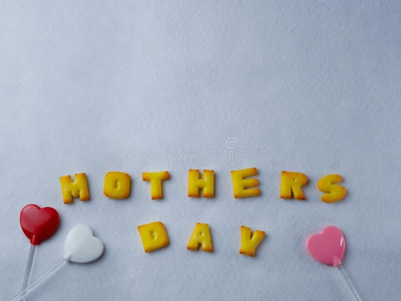 I biscotti, le lettere, le forme ed il cuore hanno modellato la lecca-lecca, sistemata su un fondo bianco per la festa della Mamm immagine stock