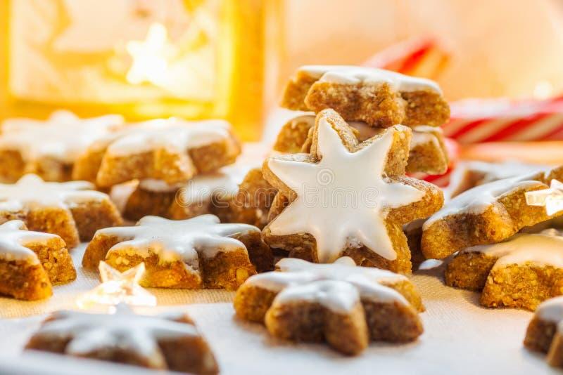 I biscotti tedeschi di Natale si dirigono le stelle lustrate al forno della cannella Magia festiva scintillante di Garland Lights immagine stock