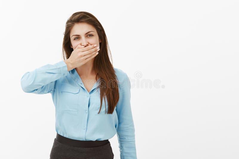 I bisogni della donna tengono la bocca chiusa Ritratto di castana femminile europeo casuale in blusa blu, coprente bocca di palma fotografia stock libera da diritti