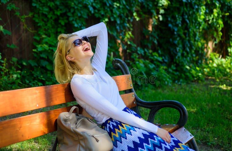 I bisogni di signora si rilassano e sognando della vacanza La ragazza si siede il banco che si rilassa nel fondo della natura di  immagini stock