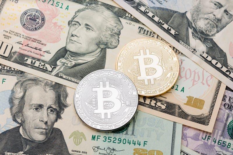 I bitcoins d'argento e dorati sul dollaro incassano il fondo fotografia stock libera da diritti