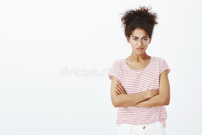I blame you in my misfortune. Angry displeased cute girlfriend in glasses and striped t-shirt, holding hands crossed on. Chest and frowning while feeling stock image