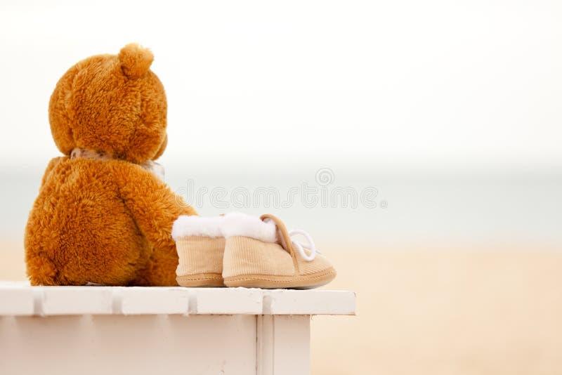 I bootees dell'orsacchiotto e del bambino di solitudine restano sull'sunbed immagine stock libera da diritti
