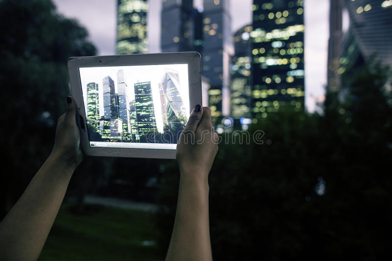 I botten som lämnas av fotoet, är händer som rymmer minnestavlan, vars skärm innehåller färgfotoet av Moskva-staden affären royaltyfria foton