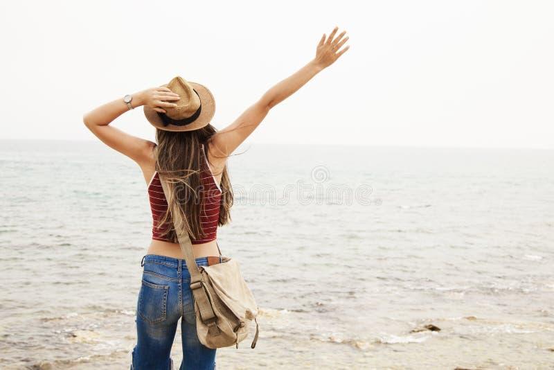 I braccia felici di condizione della giovane donna hanno sollevato le mani stese indietro e godono della vita sulla spiaggia in m immagine stock libera da diritti