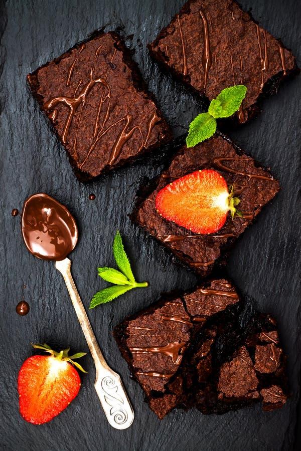 I brownie casalinghi del cioccolato fondente decorati con le fragole e la menta rimane il fondo nero dell'ardesia, vista superior immagini stock libere da diritti