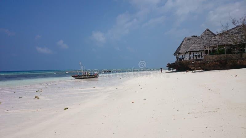 I byn av Nungwi i norden av ön av Zanzibar erbjuder fiskare ett lås, medan restaurangen på stranden vänligen arkivbild
