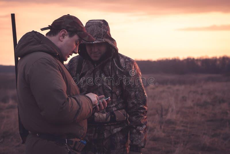 I cacciatori macchiano la loro posizione tramite smartphone nel campo rual durante la stagione di caccia immagini stock libere da diritti