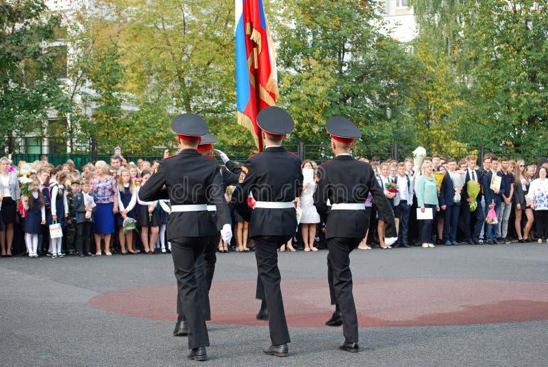 I cadetti marciano con un'insegna su un righello di mattina prima di scuola sulla parata-terra Studenti della scuola fotografie stock