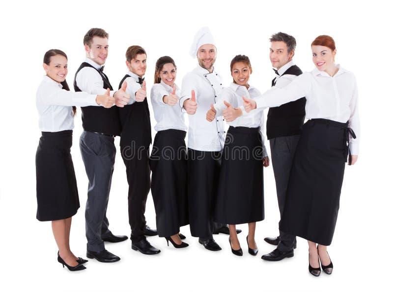 I camerieri e le cameriere di bar che mostrano i pollici aumentano il segno fotografia stock